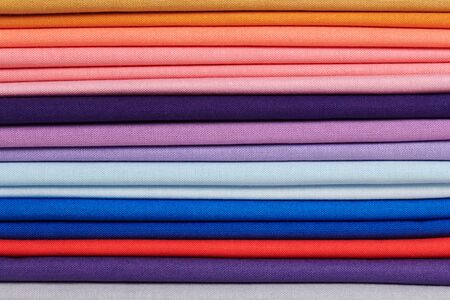 Stack of bright self-colored cotton fabrics as a background image