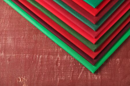 Stack of red and green fabrics on brown background, space for text 写真素材