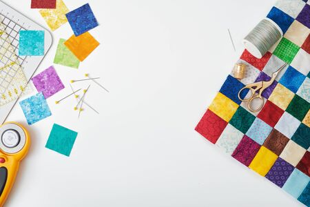 Part of quilt sewn from colorful square pieces, bright square pieces of fabric, quilting and sewing accessories