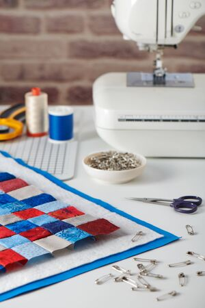 Quilt sandwich, curved basting pins, sewing machine and sewing accessories 写真素材