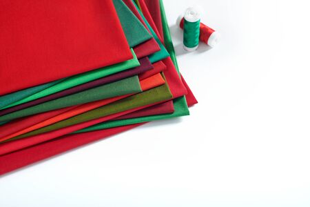 Pile of red and green fabrics and spools of thread on white background, space for text