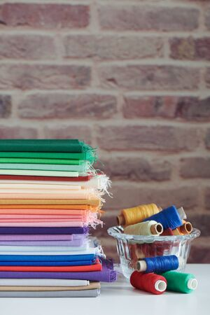 Stack of colorful monochromatic fabrics and spools of thread on brick wall background, space for text