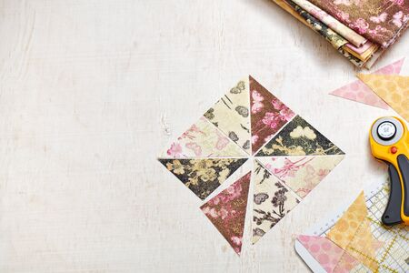Preparing of triangle pieces of fabrics for sewing quilt block, rotary cutter, rule, craft mat, stack of cloth 写真素材