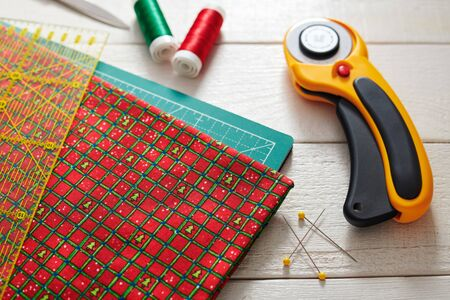 Christmas fabric and ruler on craft mat surrounded quilting and sewing accessories