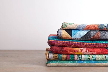 Quilts stacked on wooden table on white wall background