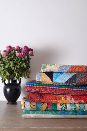 Stacked quilts and a bouquet of dried peonies in a vase on white wall background