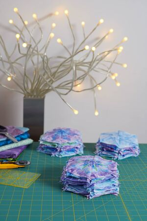Stacks of hexagonal patchwork blocks, quilting accessories, table lamp on a cutting mat 写真素材