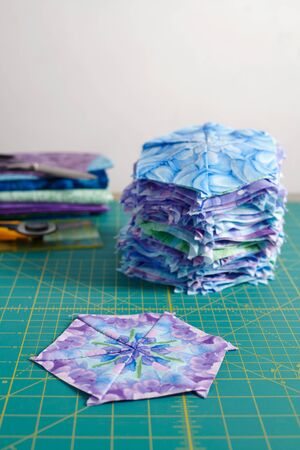 Stacks of hexagonal patchwork blocks, quilting accessories on a cutting mat 写真素材