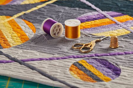 Sewing accessories lying on a mini quilt with orange-purple geometric pattern