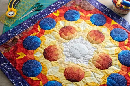 Mini quilt with the image of volumetric spheres, sewing and quilting accessories