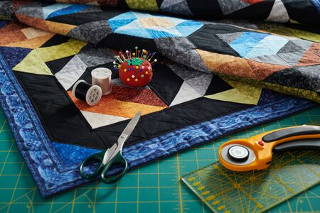 Small quilt, cutting mat and sewing and quilting accessories