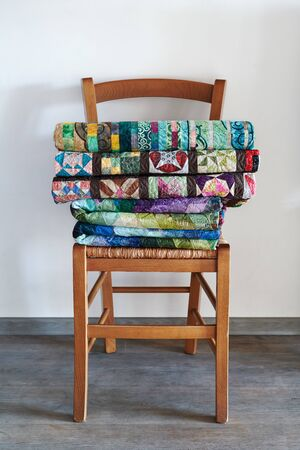 Traditional quilts stacked on wooden chair against neutral wall