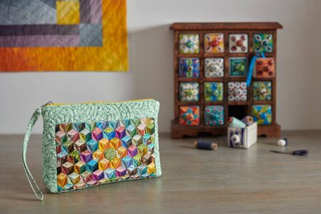 Patchwork wristlet on the backgroundwooden mini chest with ceramic drawers