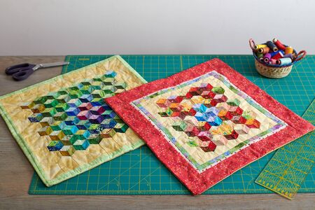 Mini quilts, basket with spools of thread, tools for patchwork and sewing on cutting mat