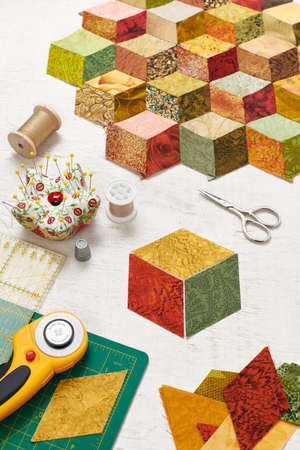 Fragment of tumbling blocks quilt, accessories for quilting on a white surface