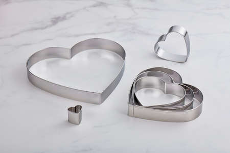 Set of stainless steel heart-shaped cookie cutters on a white marble surface