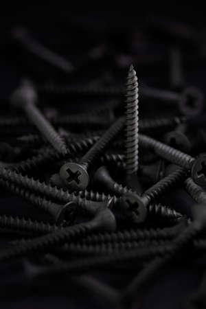 Pile of screws with flat head  , in a dark key