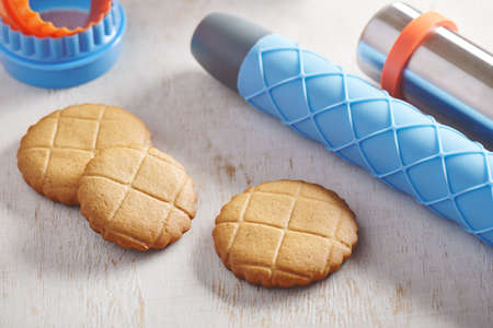 Cookies, embossing rolling pin with checkered pattern and cookie cutters on a white wooden surface Stock fotó
