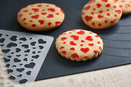 Cookies with a pattern in the form of hearts, stencil on a baking mat