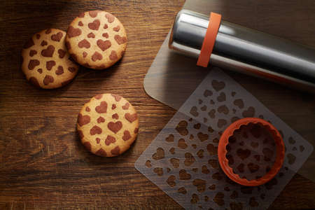 Ð¡ookies with a pattern in the shape of hearts, cookie cutter, stencil, baking mat, rolling pin on a brown wooden surface