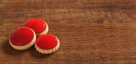 Red coated cookies on an old wooden cutting board