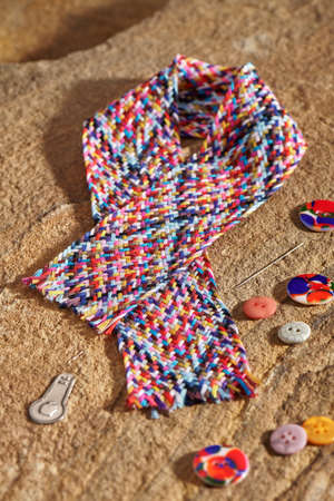 A braid of multi colored sewing threads, needle, needle threader, buttons lying on a stone Stock fotó