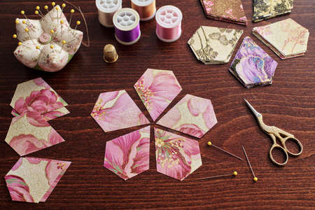 Pentagonal pieces of fabric lying in the shape of a flower, stacks of multi-colored pieces of fabric, sewing accessories on a desk
