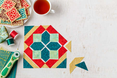 Pieces of fabric laid out in the shape of a patchwork block, a heap of cookies with a pattern imitating a patchwork block, a cup of tea, sewing and quilting accessories