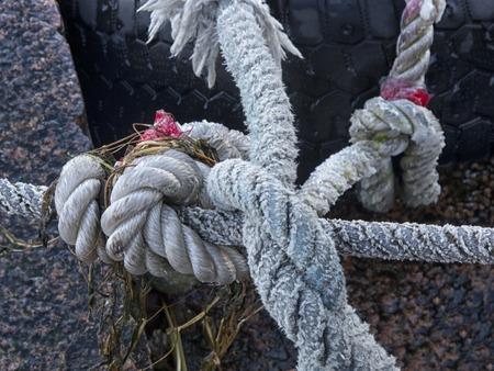 Mooring rope and bollard on sea water background