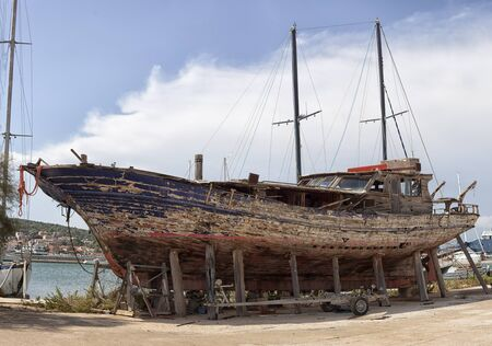 old, rusty ship waiting for repairs on the shore.