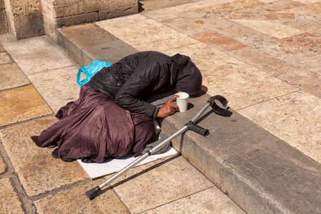 a beggar old woman lies on the steps in front of the entrance to the church