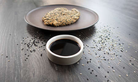 meat sprinkled with sesame seeds and fried in a pan Regional food, traditional cooking. Kitchen still life.