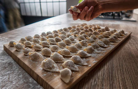 Cooking homemade dumplings or ravioli with meat on the table. Traditional Russian dumplings. Standard-Bild