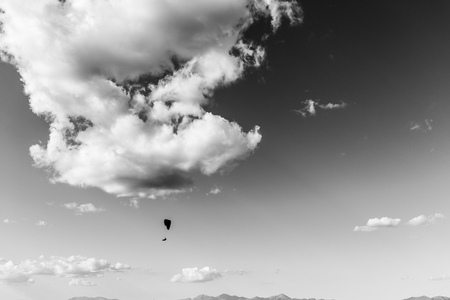 A paraglider flying against a beautiful. deep sky, with big white clouds 写真素材