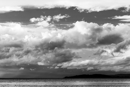 Lake on a moody day with big clouds over an island Imagens