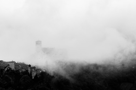 View of St. Francis papal church in Assisi (Umbria, Italy) in the middle of lifting morning fog, with some birds flying