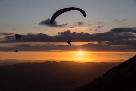Beautiful shot of two paraglider silhouettes flying over Monte Cucco (Umbria, Italy) with sunset on the background, with beautiful colors and dark tones