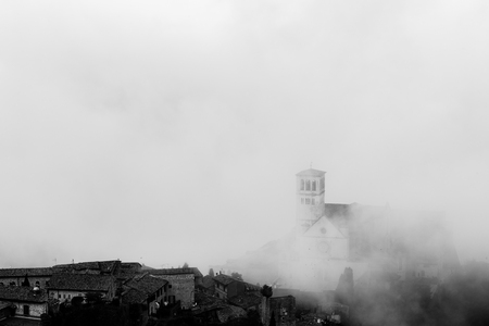View of St. Francis papal church in Assisi (Umbria, Italy) in the middle of lifting morning fog Banco de Imagens