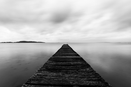 Long exposure first person view of a pier on a lake, with perfectly still water