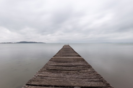 Long exposure first person view of a pier on a lake with perfectly still water