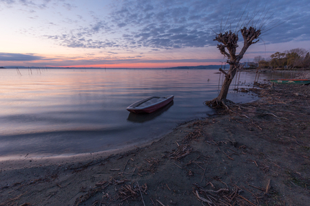 Beautiful view of Trasimeno lake (Umbria) at dusk, with a little boat near a bare tree, perfectly still water and a mackerel sky Stock Photo