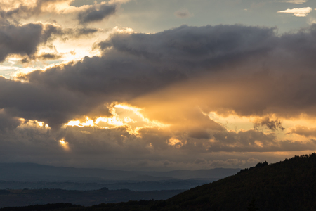 A silhouette of a mountain peak at sunset, beneath sun rays coming out through some clouds Stock Photo