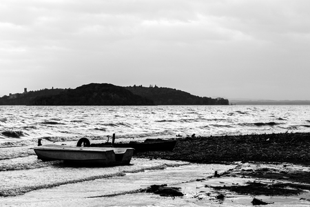 View of a lake shore on a moody day, with a little boat, islands