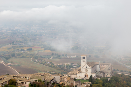 View of St. Francis papal church in Assisi (Umbria, Italy) in the middle of lifting morning fog 스톡 콘텐츠