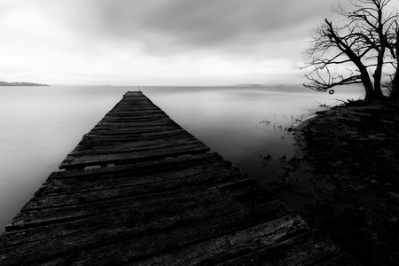 Long exposure first person view of a pier on a lake, with a tree Imagens