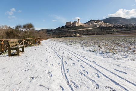 View of Assisi town (Umbria) in winter, with a country road covered by snow and a blue sky with white clouds