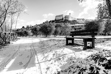 View of Assisi town (Umbria) in winter, with a country road covered by snow and sky with white clouds