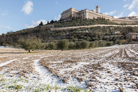 View of Assisi town (Umbria) in winter, with a field covered by snow and a blue sky with white clouds