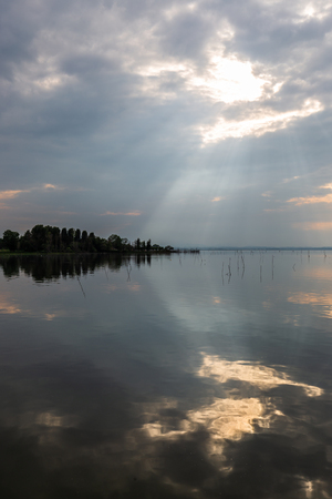 Perfectly symmetric and spectacular view of a lake, with clouds, sky and sun rays reflecting on water