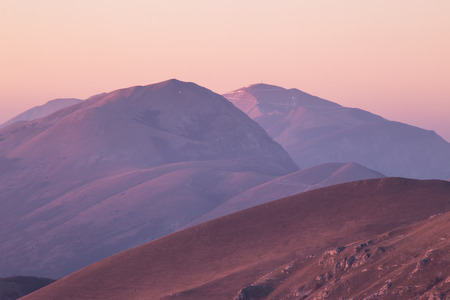A view of some mountains top, with beautiful, warm sunset colors